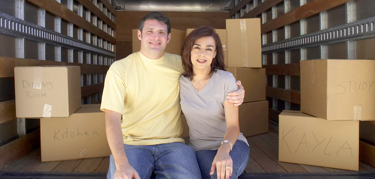 young couple in moving truck with boxes